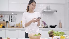 Young Asian blogger woman using smartphone photo post in social media in the kitchen, female making salad at home.