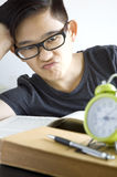 Young asian in boring face. Young asian chinese boring reading text book Stock Photography