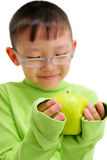 Young asian boy with a big green apple. Studio portrait of a young asian boy with a big green apple. Isolated on white. Shallow DOF. Focus on the hands and the Stock Photos
