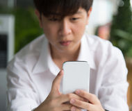 A young Asian boy chat with white smart phone  focused on the de Royalty Free Stock Photos