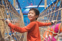 Boy climbing the net at indoor playround and smiles. Young asian boy climbing the net at indoor playround and smiles royalty free stock photo