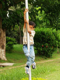 Young Asian boy climbing pole. A view of a young school age Asian boy climbing a pole in a park or front yard Royalty Free Stock Photography