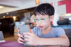 Boy doing face stress while playing games on cell ph Stock Photo