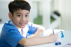 Young asian boy doing his homework.  Royalty Free Stock Photo