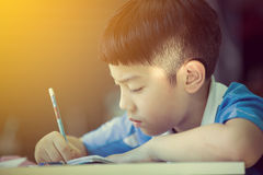 Young asian boy doing his homework. Vintage style with sun light effect Stock Photo