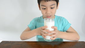 Young Asian boy drinking a glass of milk . stock footage