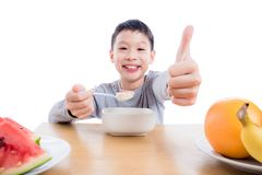 Young boy eating cereal with yogurt for breakfast. Young asian boy eating cereal with yogurt for breakfast over white background royalty free stock photography