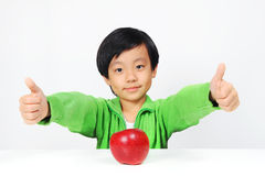 Young Asian boy gives thumbs up for healthy food. ( red apple Royalty Free Stock Photos