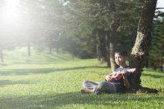 Young asian boy having fun time playing ukelele at park in the sunny morning royalty free stock images