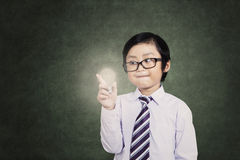 Young asian boy holds a light bulb Royalty Free Stock Photography