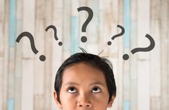 Young asian boy looking at question mark. Young asian boy looking to question mark. questions and problem concept royalty free stock photography