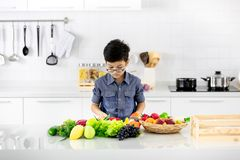 Young Asian boy looking to pile of fake fruits and vegetables in stock image