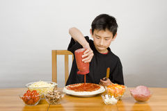 Young Asian boy making home-made pizza Royalty Free Stock Photography