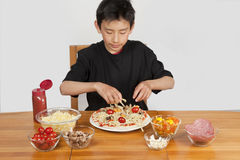Young Asian boy making home-made pizza Stock Photography