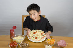 Young Asian boy making pizza Royalty Free Stock Images