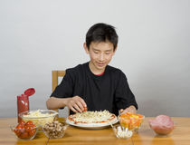 Young Asian boy making pizza Royalty Free Stock Photo