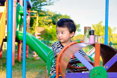 Young Asian boy play a iron train swinging at the playground und Royalty Free Stock Photo
