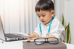 Young asian boy playing doctor and writing on diagnostic chart.  stock photos