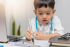 Young asian boy playing doctor and writing on diagnostic chart.  royalty free stock image