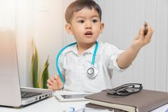 Young asian boy playing doctor and writing on diagnostic chart. Young asian boy playing doctor and writing on diagnostic chart royalty free stock photos