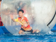 Young Asian boy playing inside a floating water walking ball Royalty Free Stock Images