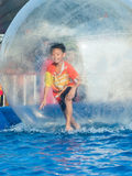 Young Asian boy playing inside a floating water walking ball Stock Photo