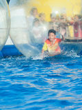 Young Asian boy playing inside a floating water walking ball Stock Image