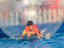 Young Asian boy playing inside a floating water walking ball Royalty Free Stock Photos