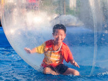 Young Asian boy playing inside a floating water walking ball Stock Photos