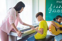 Boy playing music keyboard with his teacher in classroom. Young asian boy playing music keyboard with his teacher in classroom stock photos