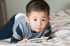 Young Asian boy playing portable console game. On his bed Royalty Free Stock Photos