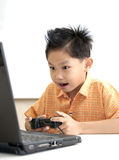 Young Asian boy plays the game with laptop. Royalty Free Stock Photography
