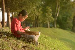 Young asian boy in red shirt reading a book near lake garden Stock Images