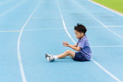 Young Asian boy sit on blue track in the stadium Stock Photography