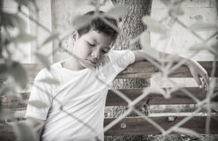 Young Asian boy sitting alone in the park. He looked scared and unsure of what he can do with his life, he is behind a fence royalty free stock images