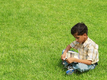 Young Asian Boy Studying. Young, Asian Indian boy, sitting on the grass reading a book Stock Images