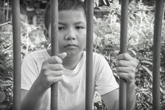 Young Asian boy trapped behind bars Stock Images