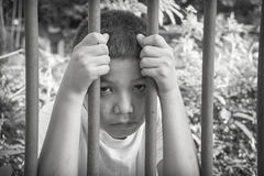 Young Asian boy trapped behind bars Royalty Free Stock Image
