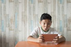 Young asian boy using digital tablet at the dining table at home with excited face. Technology / IT concept. Computer learning concept stock photography
