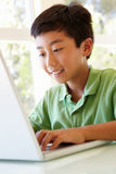 Young Asian boy using laptop Stock Images