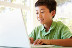 Young Asian boy using laptop Stock Photo
