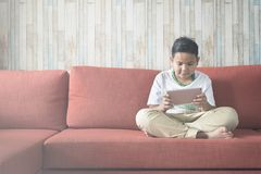 Young asian boy using laptop computer while sitting cross-legged on a sofa at home. Royalty Free Stock Photos