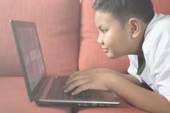 Young asian boy using laptop computer on a sofa at home. Royalty Free Stock Photography