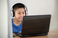 Young Asian boy using laptop technology Royalty Free Stock Image