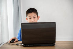 Young Asian boy using laptop technology at home. copyspace. Young Asian boy using laptop technology at home stock photo