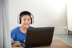 Young Asian boy using laptop technology at home. copyspace Stock Photos