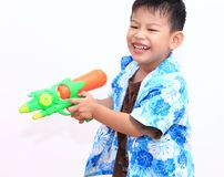 Young Asian boy with water gun on white background.child playing. Fun with the water gun in Songkran holiday royalty free stock images