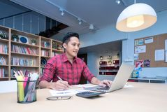 Young asian business entrepreneur record  revenue profit to smart computer. At home office.Conceptual for startup small businesses entrepreneur and freelance Stock Images