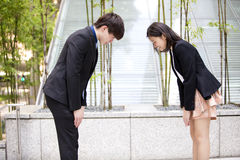 Young Asian business executives bowing to each other royalty free stock photo