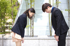 Young Asian business executives bowing to each other royalty free stock photography